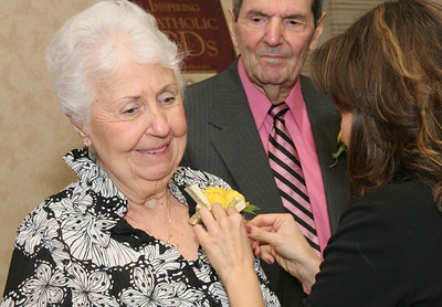 Julianna Barroso, right, of the Office of Formation and Discipleship, pins the anniversary corsage on Marilyn Meyer as her husband of 60 years, William, looks on.