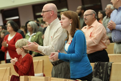 Paul Miller, center, and his children Stuart, 8, and Rachel, 14, join the congregation in singing the AIDS Mass closing hymn.  (Page 13, December 9, 2010 issue)