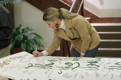 "Keri Ninness, an HIV social worker at Grady Hospital, Atlanta, signs the banner with the names of ""Those Who Touched Us."" St. Ann parishioner and AIDS ministry member Diane Calabrese-Tanger carried the banner into the church during the opening procession.  (Page 12, December 9, 2010 issue)"