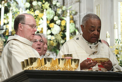 Deacon Gerald Zukauckas, left, and Archbishop Wilton D. Gregory stand before the altar during The Great Amen.