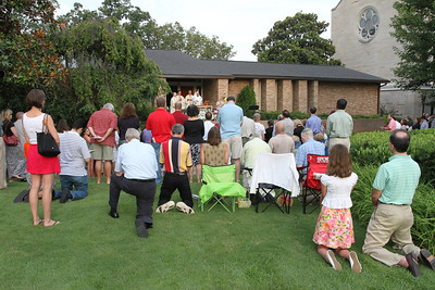 People gathered on the lawn and driveway between the Cathedral of Christ the King rectory and Peachtree Road during the Aug. 15 Mass observing the 75th anniversary of Christ the King's first Mass. The late Father Joseph P. Moylan was the main celebrant for the first Mass.  (Page 23, September 29, issue)