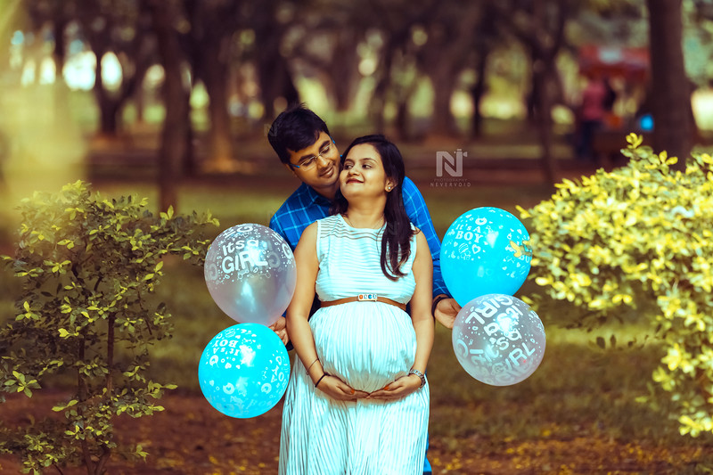 New parents with It's a boy and It's a girl balloons in their photoshoot