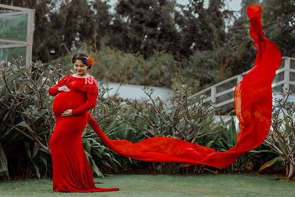 Classic red gown with long trail flaunt by a gorgeous mom-to-be