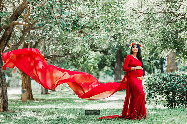 Long trail red flying gown worn by mom-to-be