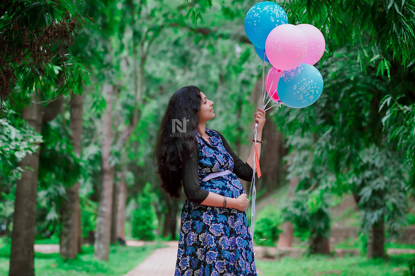 It's a boy, and it's a girl balloons in a maternity photoshoot