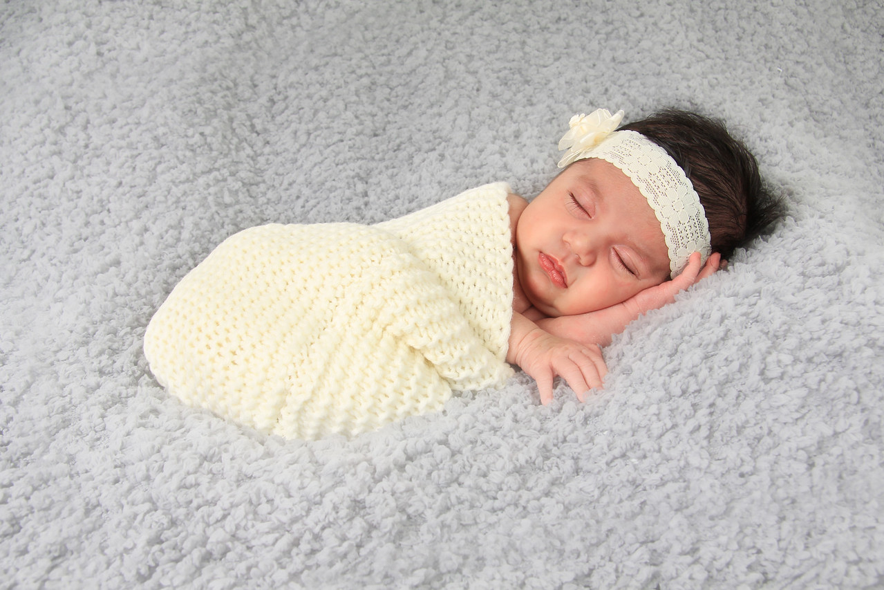Newborn baby girl of Caucasian and Asian heritage wearing a lace head band.