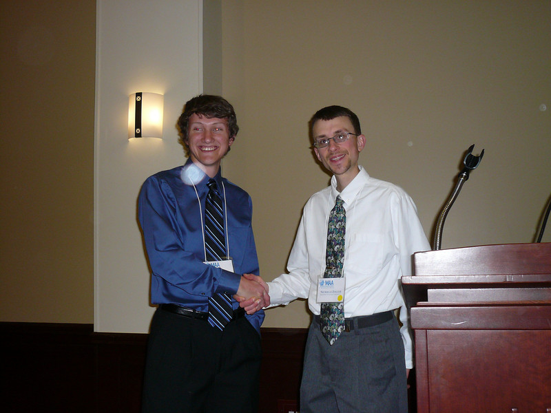Dr. Zoller congratulates Jeremy on finishing in first place in the student research paper competition