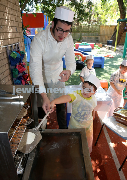 Matzah Bakery at Hug A Bub. Yisroel Lehrer helps Moshe Banisti put his matzah in the oven. Pic Noel Kessel.