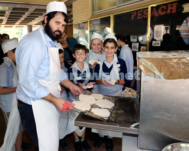 Matzah Bakery at Masada Primary School. Rabbi Elimelech Levy places a tray of Matzahs into the oven, as Josh Neiman, Ari Kind, Asher Rudnick look on. Pic Noel Kessel