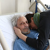Maurice La-Garde's a hug from his wife Heike Petermann while in his bad at the Whittier Rehabilitation Hospital in Haverhill on Thursday morning. Maurice has been a quadriplegic since a 1987 swimming pool accident and recently contracted a flesh-eating bacteria and has been stuck in a rehab facility ever since. He and his family are desperate to bring him home before Christmas, and are trying to raise $40,000 to get the equipment he needs to make that possible. SUN/JOHN LOVE
