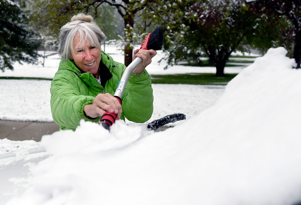 . Janie Stuart, of Boulder, scrapes snow off her windshield on Thursday in Boulder, Colo. Jeremy Papasso/ Staff Photographer/ May 18, 2017