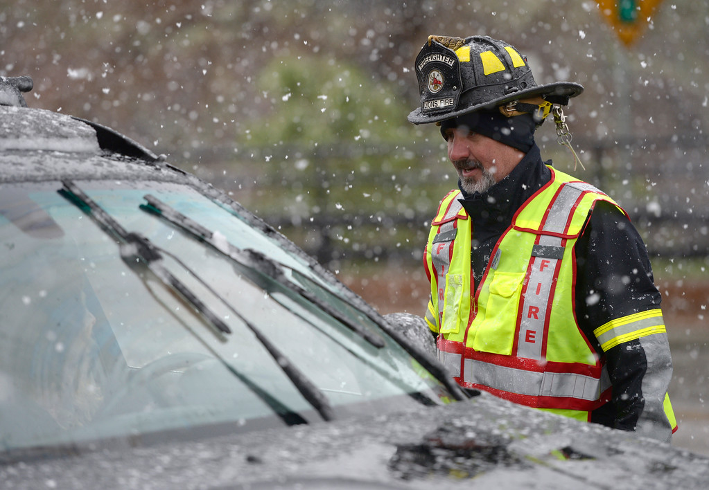 . Lyons firefighter Gregory Schrodt redirects a motorist on U.S. 36., near Planet Bluegrass, in Lyons Thursday afternoon, while the highway was closed up to Estes Park due to heavy snow. Lewis Geyer/Staff Photographer May 18, 2017