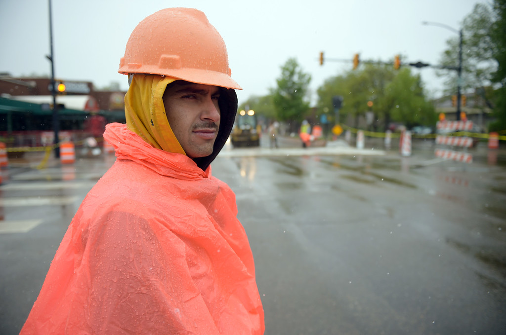 . Flagger Felipe Porras stands in the wintry weather at Sixth Avenue and Main Street Thursday morning as work continues on the Main Street construction work. Lewis Geyer/Staff Photographer May 18, 2017