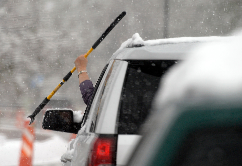 . A woman uses a scraper to get snow off her windshield while at a stop light on Thursday in Boulder, Colo. Jeremy Papasso/ Staff Photographer/ May 18, 2017