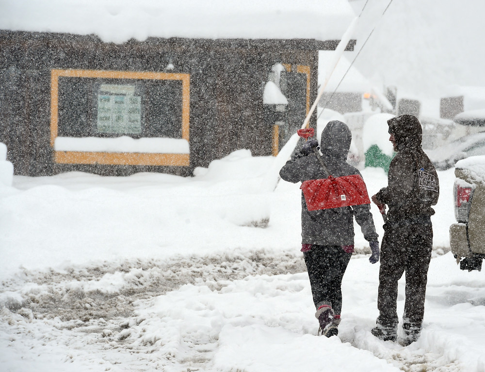 . Emily Weir, left, and Barrac Elgee, head to their home for snow shoveling during a steady snow  in Nederland. For more photos, go to www.dailycamera.com.  Cliff Grassmick  Staff Photographer May 18, 2017