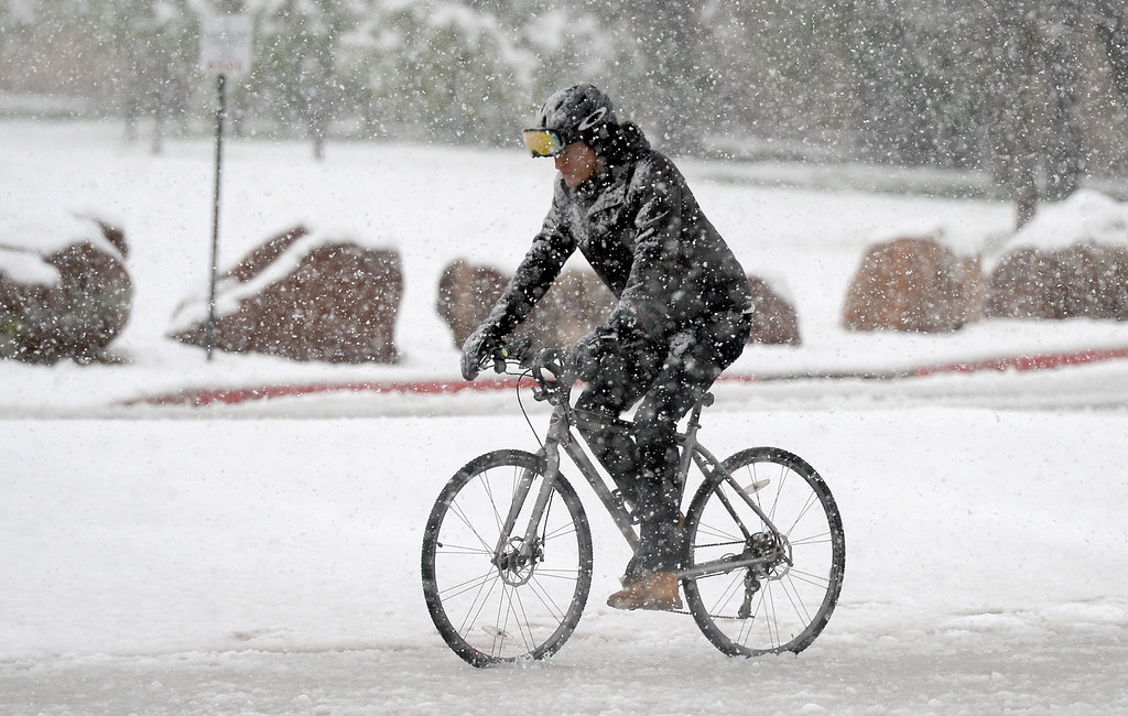 . A cyclist rides his bicycle in the snow on Thursday in Boulder, Colo. Jeremy Papasso/ Staff Photographer/ May 18, 2017