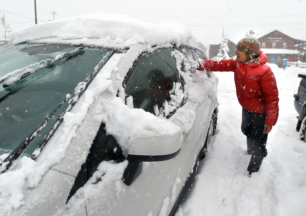 . Shannon Tupa cleans off her car with her hands in Nederland. She had put away her snow scraping gear. For more photos, go to www.dailycamera.com.  Cliff Grassmick  Staff Photographer May 18, 2017