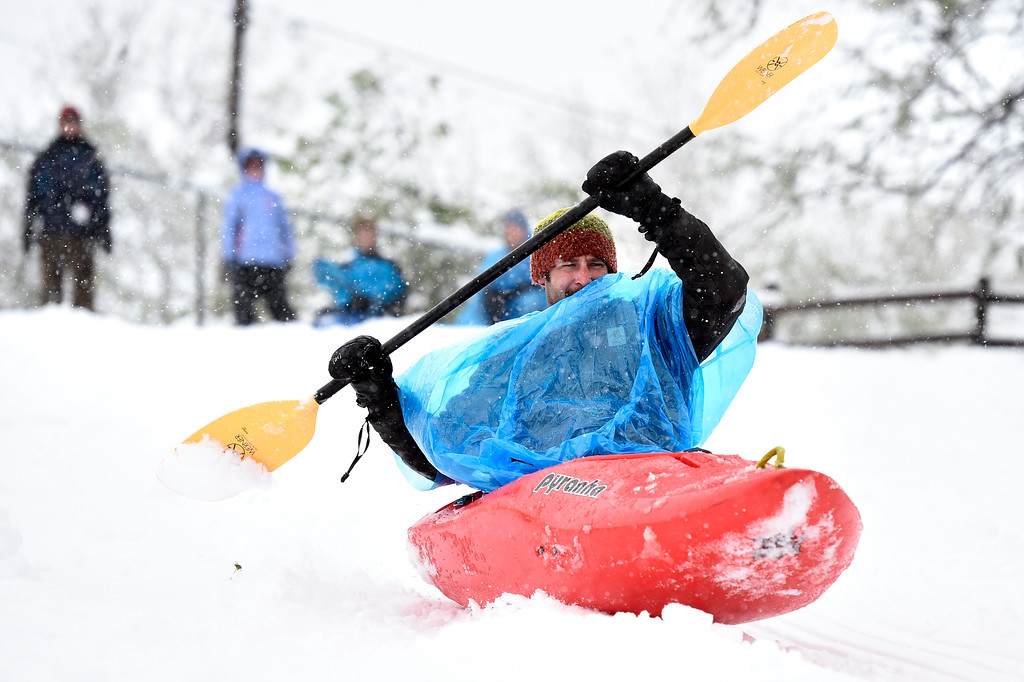 . Justin Shannon, of Chico, Cali., uses a kayak to sled down the hill at Tantra Park on Thursday in Boulder, Colo. Jeremy Papasso/ Staff Photographer/ May 18, 2017