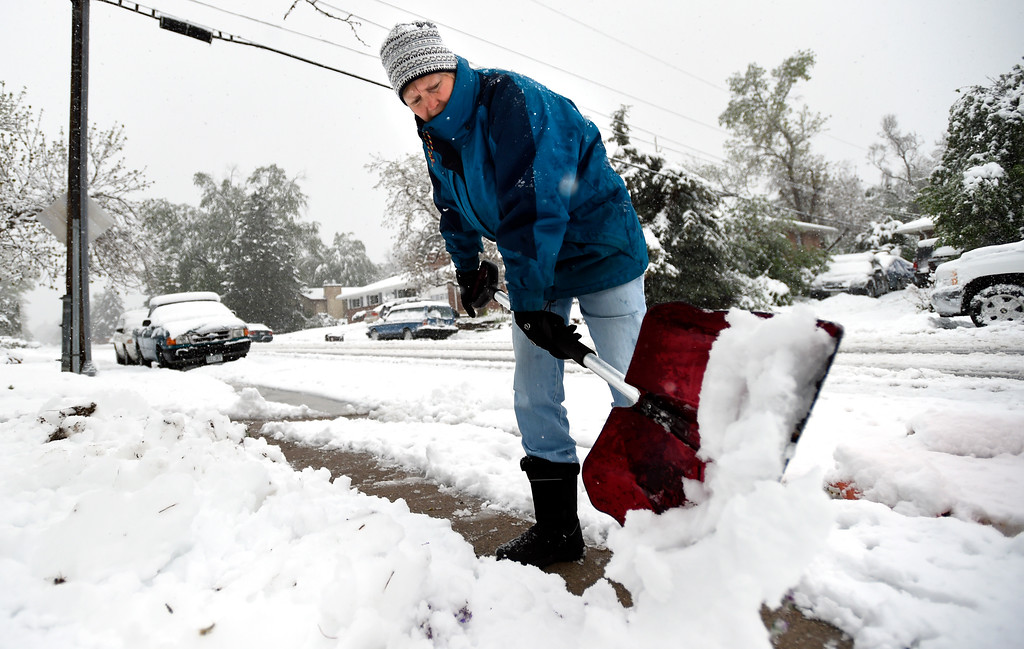 . Susan Sullivan, of Boulder, shovels the sidewalk in front of her house on Emerson Street in the spring snowstorm on Thursday in Boulder, Colo. Jeremy Papasso/ Staff Photographer/ May 18, 2017