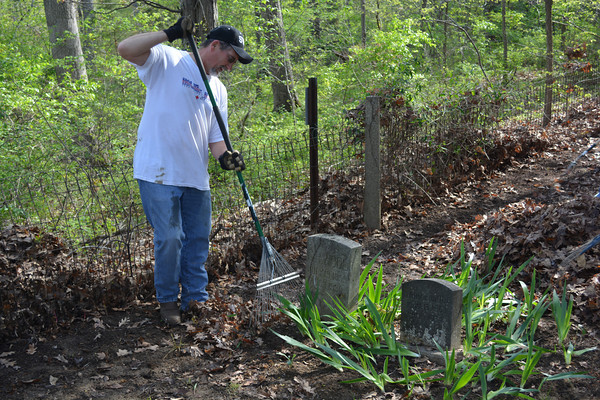 Randy Arnold rakes leaves near some old graves at the old Loy Chapel Cemetery south of Effingham.
