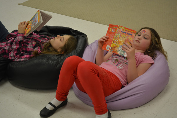 Second-graders Elora Steele, left, and Hadley Hagler enjoy some books during Family Reading Night at Beecher City Grade School.