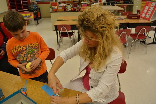 Beecher City Grade School Title I reading teacher Annette McDaniel makes a bookmark as first-grader Kiel Moeller looks on during Family Reading Night at the school