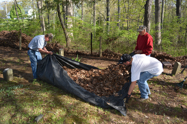 Clockwise from left, Ted Tedrick, Jack Arnold and Randy Arnold gather raked leaves at the Loy Chapel Cemetery for disposal.