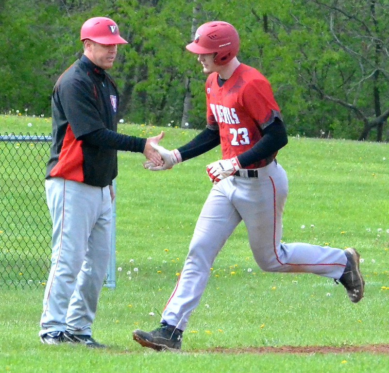 . KYLE MENNIG - ONEIDA DAILY DISPATCH Vernon-Verona-Sherrill\'s Davey Moffett (23) is greeted by coach Chad Hodkinson as he rounds third after hitting a home run against Oneida during their game in Oneida on Tuesday, May 9, 2017.