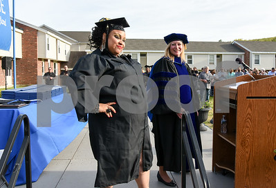 051217  Wesley Bunnell | Staff  Lincoln College New England held their commencement exercises for new graduates on Friday evening on campus. Mortuary Science Graduate Jenna Glasper poses for the camera after performing the National Anthem while standing next to college President Denise Lewicki.