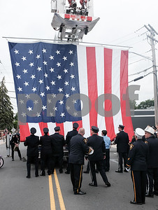 052917  Wesley Bunnell | Staff  Plainville held their annual Memorial Day Parade on Monday morning followed by a memorial unveiling dedicated to Gold Star Families at Veterans Memorial Park. Plainville firefighters all help attach and hang a large American flag to a ladder truck.