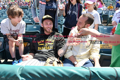 051617  Wesley Bunnell | Staff  The New Britain Bees vs the Bridgeport Bluefish in the 2nd game of a double header played early afternoon on Tuesday. Nate Roe (13) signs autographs as he sits with a childhood friend in the stands before the start of the game.