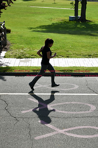 051617  Wesley Bunnell | Staff  A runner is silhouetted as she runs past ribbons in the asphalt in Walnut Hill Park on Tuesday afternoon.