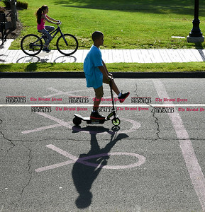 051617  Wesley Bunnell | Staff  Children are silhouetted as they ride and skate past ribbons in the asphalt in Walnut Hill Park on Tuesday afternoon.