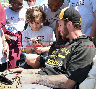 051617  Wesley Bunnell | Staff  The New Britain Bees vs the Bridgeport Bluefish in the 2nd game of a double header played early afternoon on Tuesday. Nate Roe (13) teaches a young fan named Alex how to sign a sports card that Alex carries in his wallet of himself.