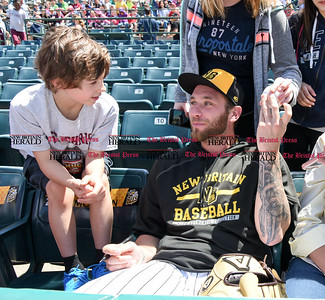 051617  Wesley Bunnell | Staff  The New Britain Bees vs the Bridgeport Bluefish in the 2nd game of a double header played early afternoon on Tuesday. Nate Roe (13) signs autographs as he sits in the stands before the start of the game.