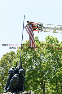 051817  Wesley Bunnell | Staff  Newington firefighter Alex Sierra takes down a worn flag from the Iwo Jima Memorial on Thursday afternoon. 95 year-old Iwo Jima Survivor George Caron along with his wife Lois purchased the custom made 48 star flag to replace the worn flag.