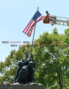 051817  Wesley Bunnell | Staff  Newington firefighter Alex Sierra unfolds and prepares to attach a new flag above the Iwo Jima Memorial on Thursday afternoon. 95 year-old Iwo Jima Survivor George Caron along with his wife Lois purchased the custom made 48 star flag to replace the worn flag that was being used.