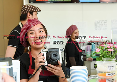 050217  Wesley Bunnell | Staff  Yo Yo Ice Cream held their ribbon cutting ceremony with Mayor Erin Stewart and city officials. Jessie Ouyang gets her instant camera ready for the ribbon cutting.