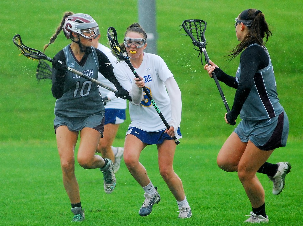 . Cazenovia sophomore midfielder Ava Hartley takes up the ball while defended by Clinton sophomore midfielder Wiley Gifford (right) and Clinton junior midfielder Sarah Owens (left) Saturday, May 19 at Cazenovia.