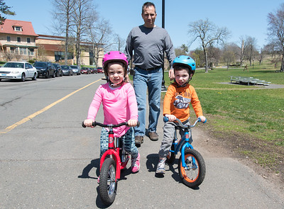05/01/18  Wesley Bunnell | Staff  Nicholas Eliades follow walks behind his twins Emma and George, age 3, as they ride their bikes around Walnut Hill Park on a warm Tuesday afternoon.