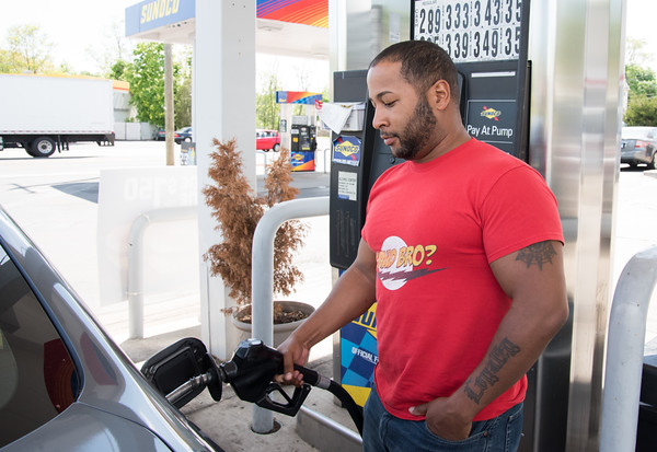 05/14/18 Wesley Bunnell | Staff Justin Douglas pumps gas at the Sunoco at the intersection of West Main St and Corbin Ave on Monday afternoon.