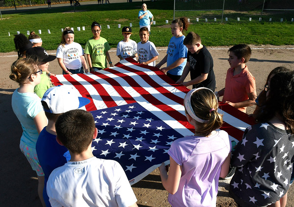 5/23/2018 Mike Orazzi | Staff Community Club students hold the American flag during the 2nd Annual South Side School Warrior Walk Wednesday evening in honor of Connor Albert, a student who died of cancer in December.