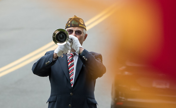 05/28/18 Wesley Bunnell | Staff A packed parade route greeted marchers in the 2018 Memorial Day Parade in Southington on Monday morning. A trumpeter is seen through a waving american flag as he plays TAPS.
