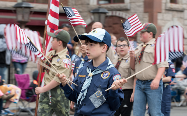 05/28/18 Wesley Bunnell | Staff A packed parade route greeted marchers in the 2018 Memorial Day Parade in Southington on Monday morning. A boy scout twirls multiple american flags as he marches down Main St.