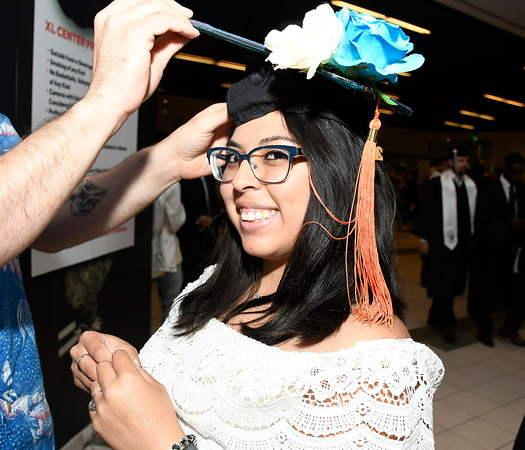 5/19/2018 Mike Orazzi   Staff Megan Gilstrap gets some help with her cap while at the XL Center for the CCSU commencement ceremony Saturday in Hartford.