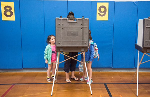 05/22/18 Wesley Bunnell | Staff Nicole Bacon votes at Hubbard School as daughter Harper, age 4 L, and daughter and Hubbard student Avery, age 5 look on. Voting took place for the Berlin on Tuesday for the town and education budgets.
