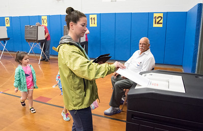 05/22/18  Wesley Bunnell | Staff  Nicole Bacon enters her ballot at Hubbard School as daughter Harper, age 4, looks on.   Voting took place for the Berlin on Tuesday for the town and education budgets.