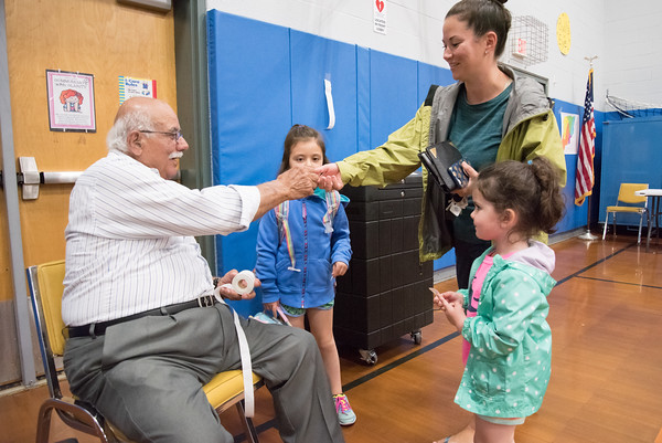 05/22/18 Wesley Bunnell | Staff Tabulator Peter Dizes hands Nicole Bacon and daughters , Avery, age 5 and Harper , age 4, receive voting stickers as well. Voting took place for the Berlin on Tuesday for the town and education budgets.