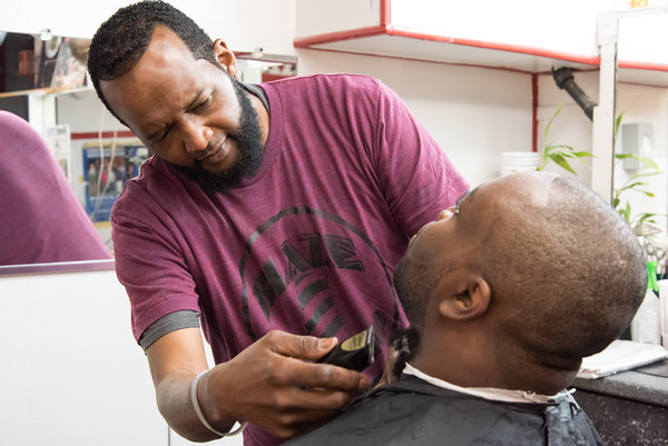05/24/18 Wesley Bunnell | Staff Maurice Robinson finishes trimming a client at Blaze Barbershop on West Main St on Thursday afternoon. The barbershop is a place of discussion everyday including topics as the NFL's recent decision to require on field personnel to stand for the National Anthem.