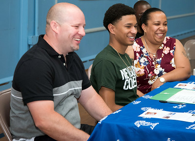 05/25/18  Wesley Bunnell | Staff  Francisco Santiago II from E.C. Goodwin High School signed his papers to attend and play basketball for Newbury College. Parents Francisco Santiago Sr and Marsha Michaud sit on either side of him.